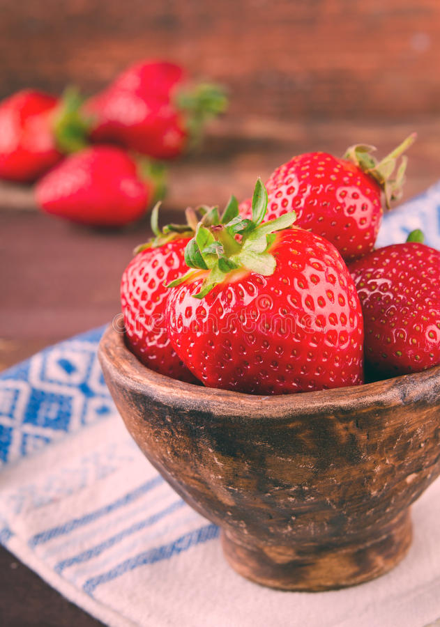 Ripe fresh juicy organic strawberries in old clay bowl stock images