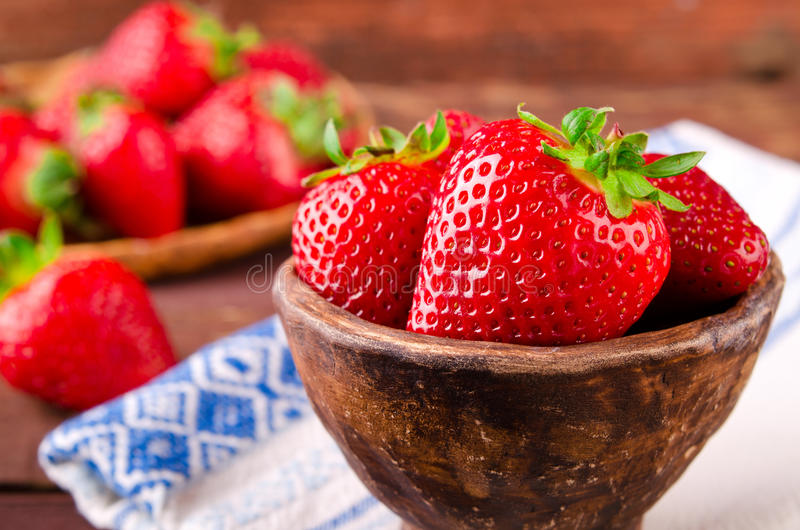 Ripe fresh juicy organic strawberries in old clay bowl stock photography