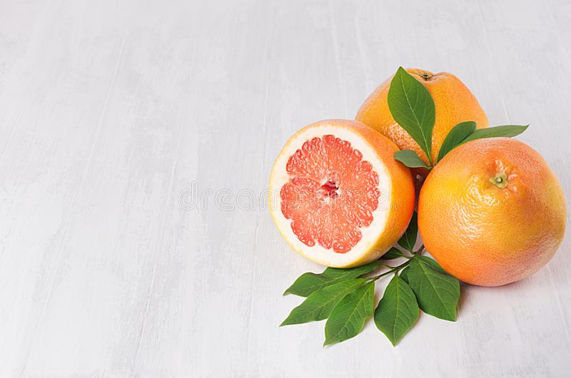 Ripe fresh orange grapefruits and half slice with green leaf on white wood board, top view. Healthy food background. royalty free stock photos