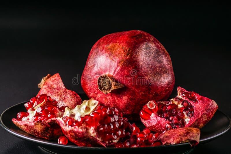 Ripe fresh pomengranate fruit, on black background. stock photography