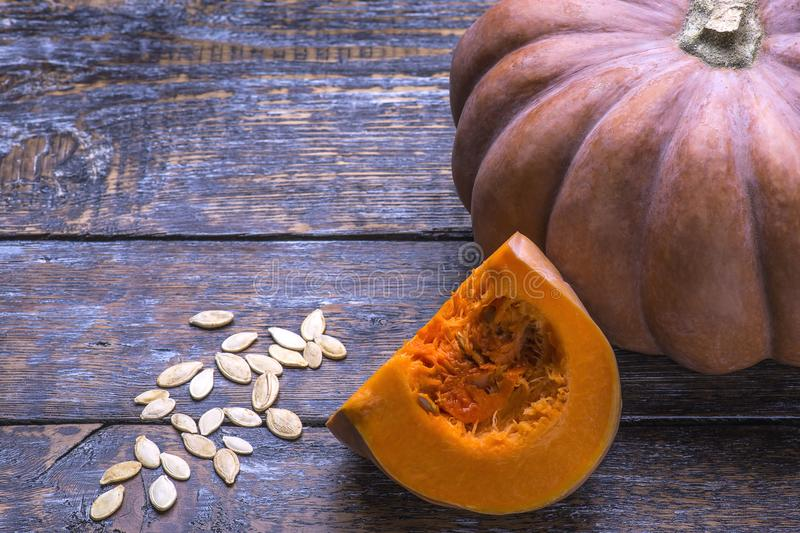 Ripe fresh pumpkin with seeds on a wooden background. Natural vegetarian food for healthy eating. stock images