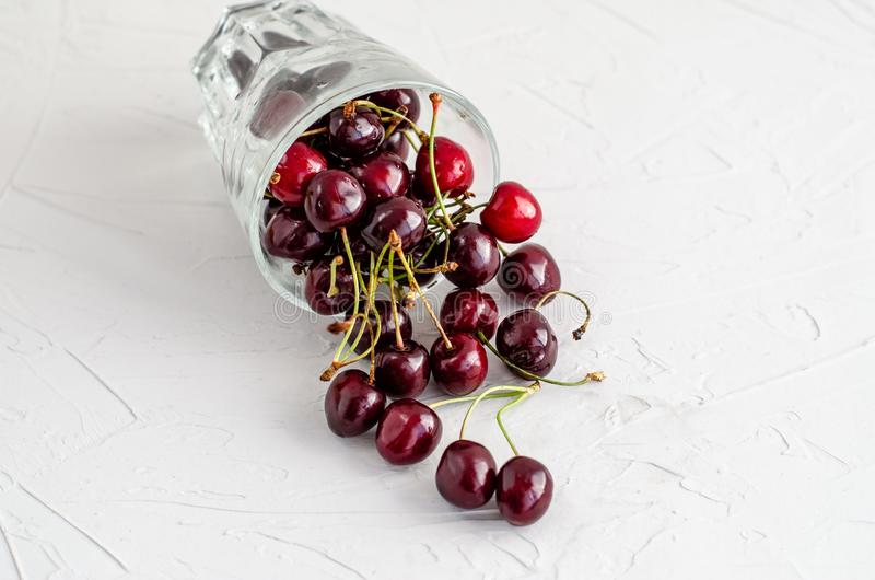 Ripe fresh red sweet cherry poured from an inverted glass cup on a white concrete background royalty free stock photography