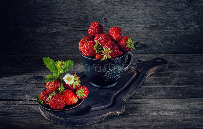 Ripe fresh strawberries in a clay pot in a rustic style. Art. royalty free stock image