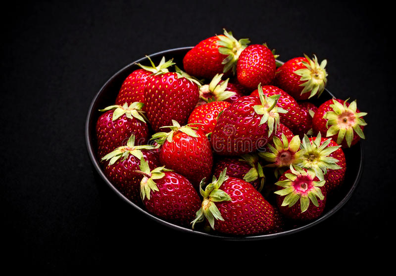 Ripe fresh strawberry in bowl on black stock image