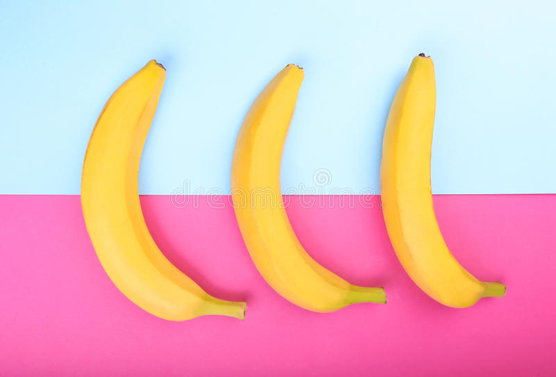 Ripe, fresh and sweet yellow bananas on a bright pink and light blue background. Tropical bananas. Banana, close-up. stock photo