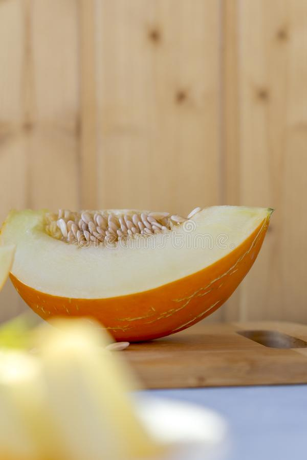 Ripe fresh yellow melon cut into pieces on a blue background stock photography