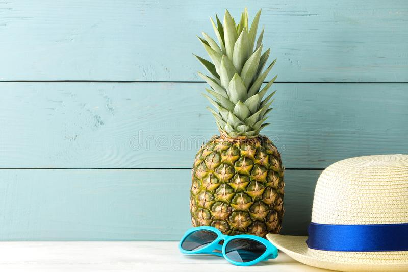 Ripe fruit pineapple and beach accessories, sunglasses and hat on a blue wooden background. summer. space for text stock photography