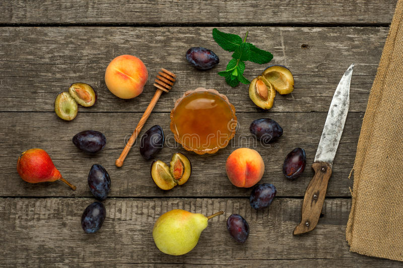 Ripe fruits of peach, plums and pear with honey in stock images
