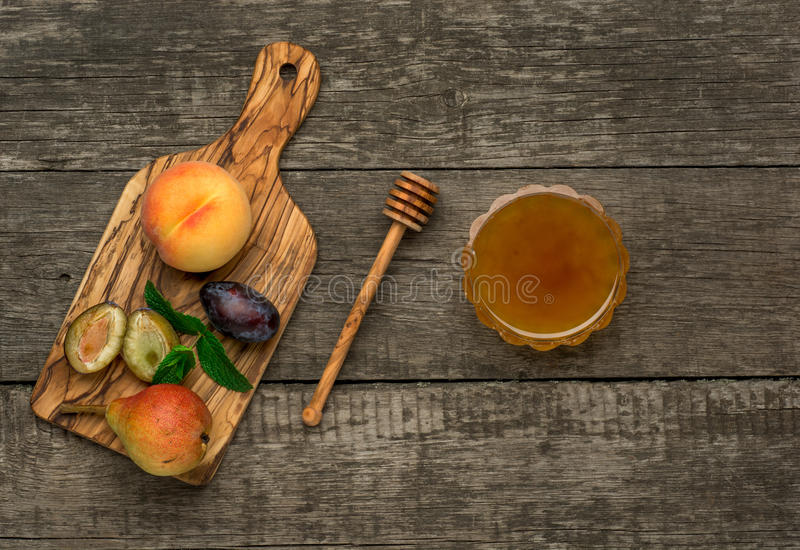 Ripe fruits of peach, plums and pear with honey in royalty free stock photos