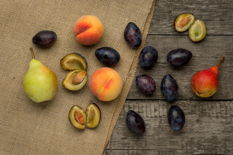Ripe fruits of peach, plums and pear on rustic royalty free stock images