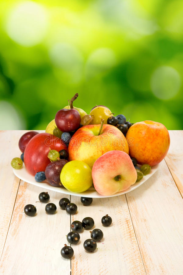Ripe fruits on a plate. On a blurred background royalty free stock photos