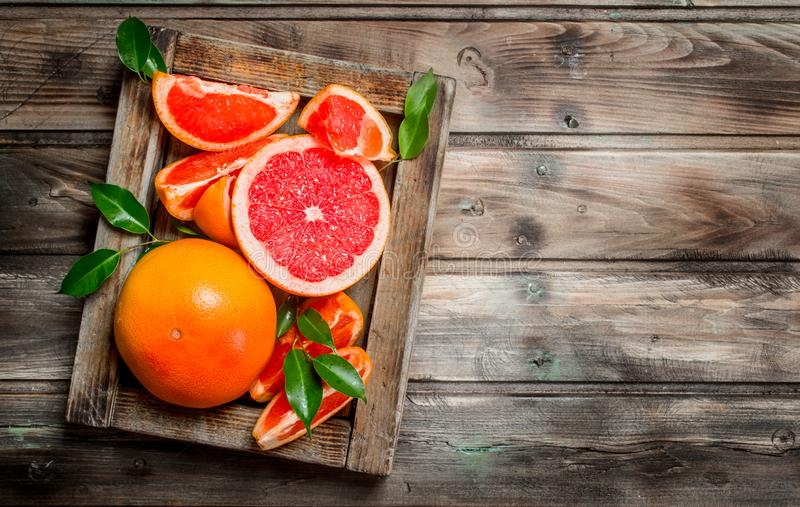 Ripe grapefruit on a wooden tray. On wooden background royalty free stock images