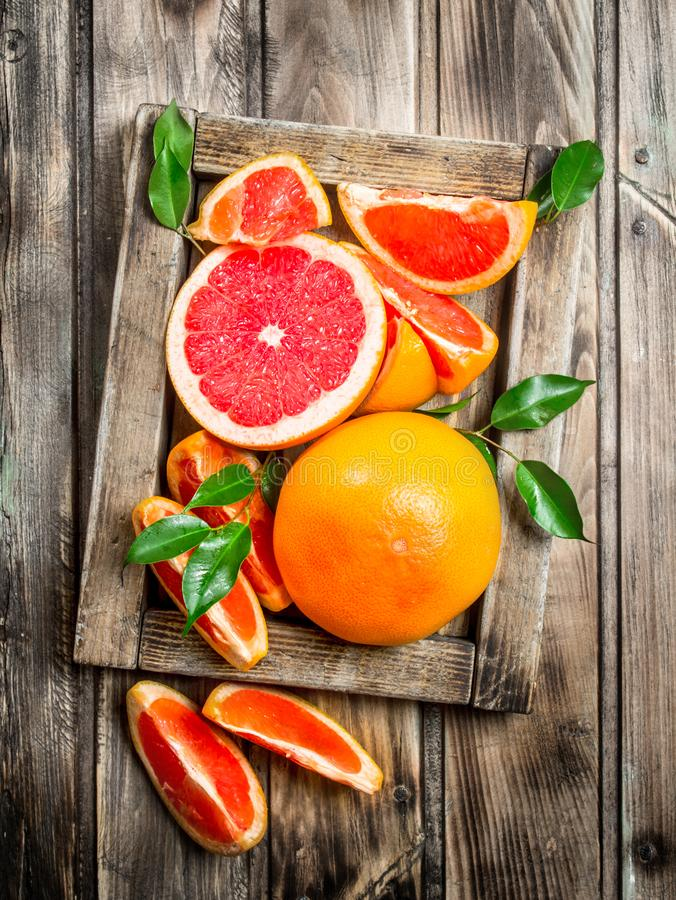 Ripe grapefruit on a wooden tray. On wooden background stock images
