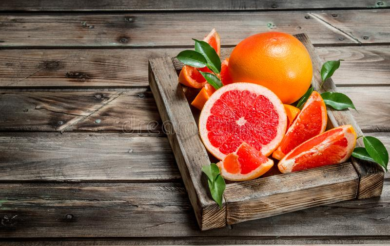 Ripe grapefruit on a wooden tray. On wooden background stock photos