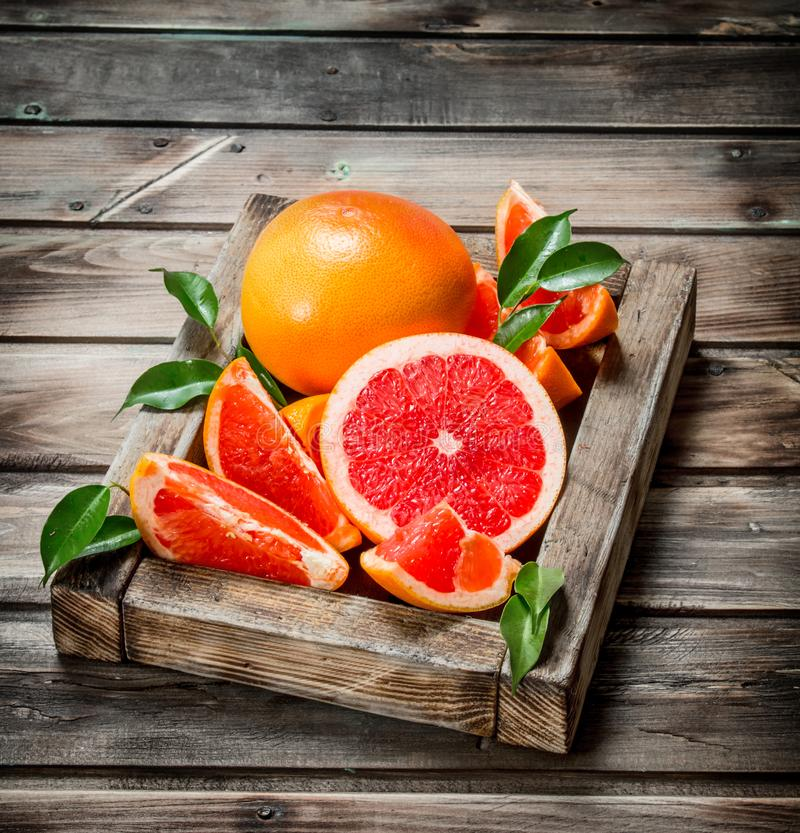 Ripe grapefruit on a wooden tray. On wooden background stock photography