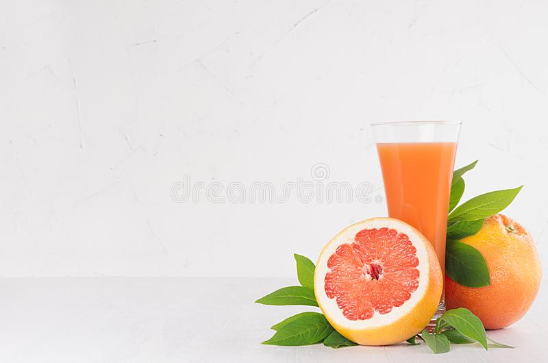Ripe grapefruits with half slice, green leaves and juice on soft white modern kitchen interior. Healthy fruits summer background. Ripe grapefruits with half royalty free stock photography