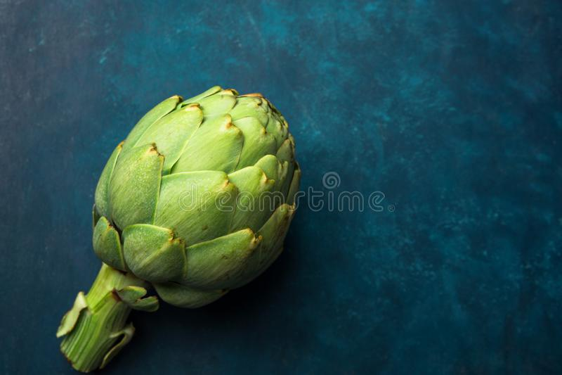 Ripe green artichoke on dark blue background. Creative food poster. Minimalist style. Mediterranean Spanish cuisine. Healthy plant based diet superfoods concept royalty free stock photo