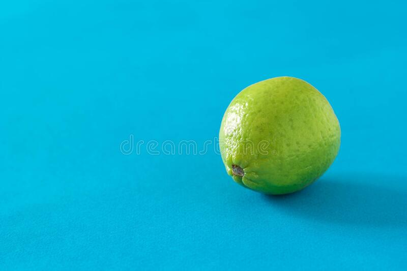 Ripe green lime on a blue background. royalty free stock photo