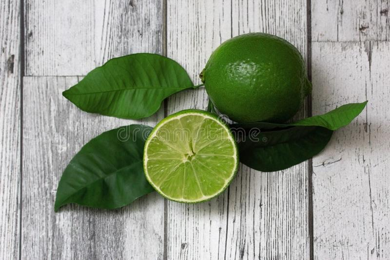 Ripe green limes with leaves on a gray wooden background. Citrus fruit. The ingredients for a cocktail. stock image