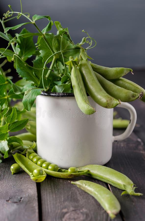 Ripe Green peas on wooden table. Heap of young green peas whole and broken with leaves and flower in vintage cup over old wooden table. Dark rustic style stock image