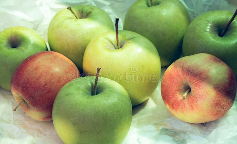 Ripe green and red apples with sunny light on paper background royalty free stock photography