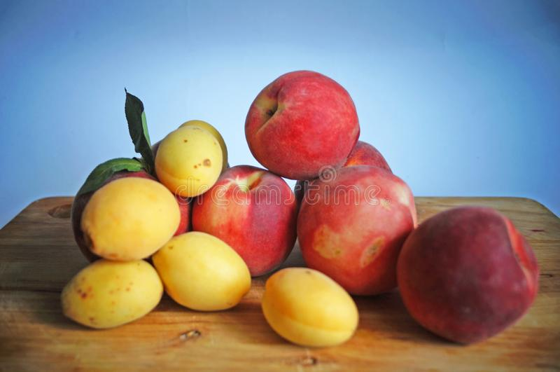 Ripe and juicy apricots and peaches with yellow and orange peels royalty free stock photography