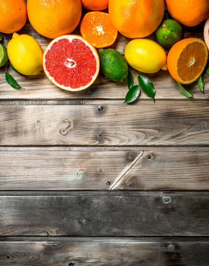 Ripe juicy citrus with leaves. On wooden background stock photo