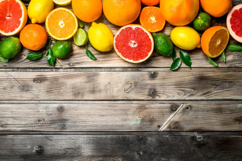 Ripe juicy citrus with leaves. On wooden background stock images