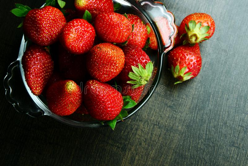 Ripe Juicy and Fresh Strawberry in a bowl on wooden background royalty free stock photo