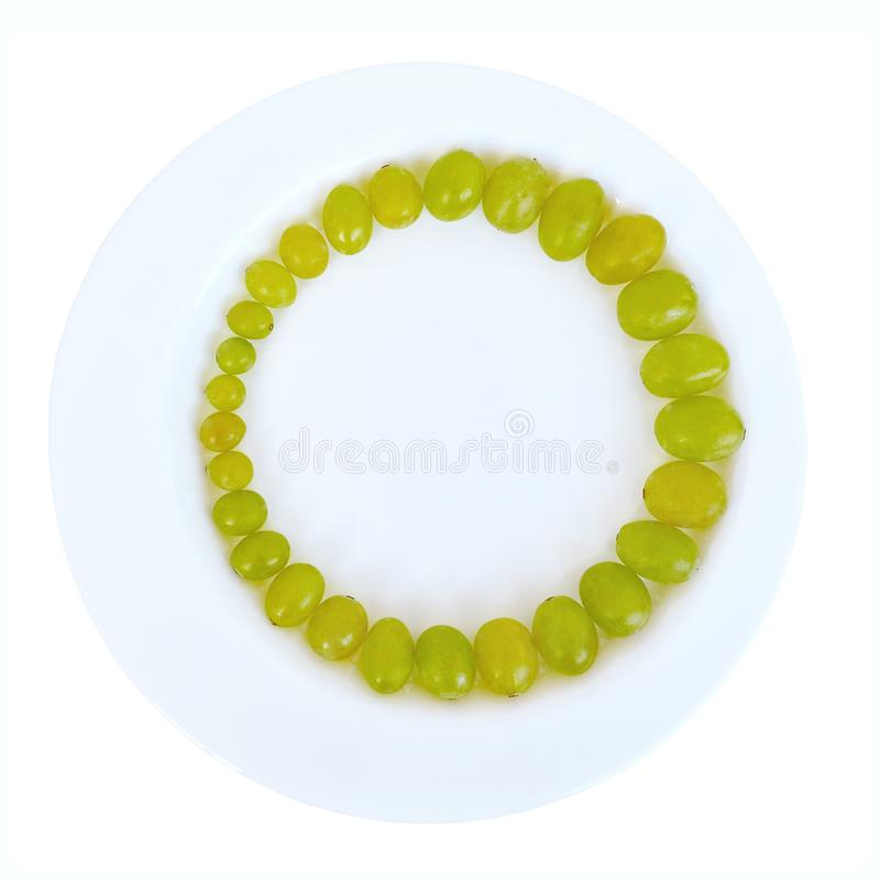 Ripe juicy green grapes lined with ring in order of increasing size of berries in a white plate, top view, isolated stock images