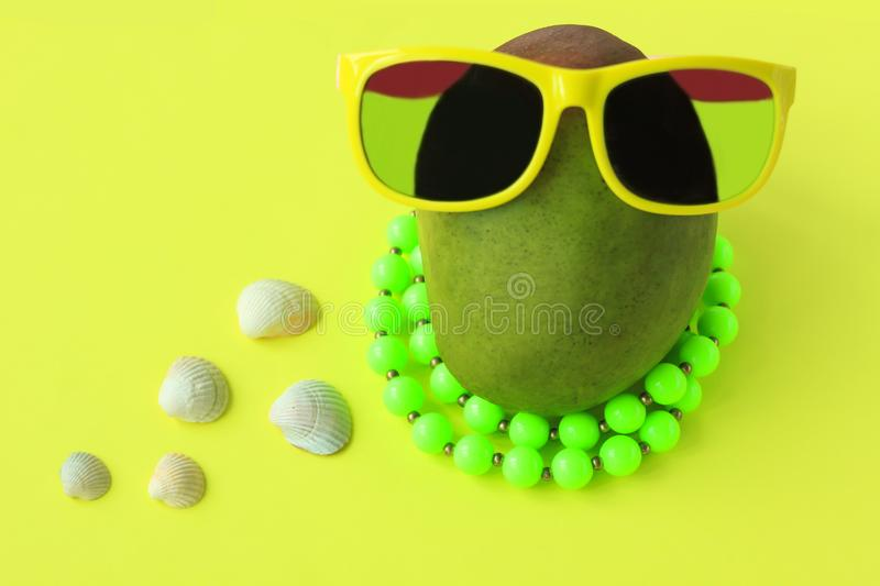 Ripe juicy green and red mango in sunglasses and beads on pastel yellow background.Copy space. minimalistic style. Ripe juicy green and red mango in yellow royalty free stock image
