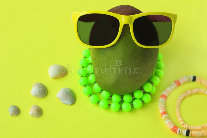 Ripe juicy green and red mango in sunglasses and beads on pastel yellow background.Copy space. minimalistic style. Ripe juicy green and red mango in yellow royalty free stock images