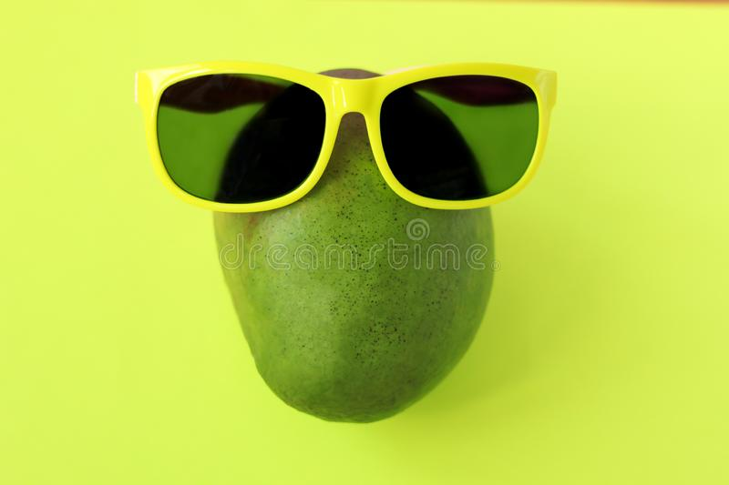 Ripe juicy green and red mango in sunglasses on pastel yellow background.Copy space. minimalistic style. Ripe juicy green and red mango in yellow sunglasses on royalty free stock photo