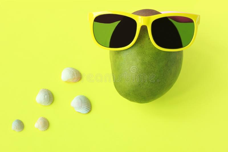 Ripe juicy green and red mango in sunglasses on pastel yellow background.Copy space. minimalistic style. Ripe juicy green and red mango in yellow sunglasses on stock photography