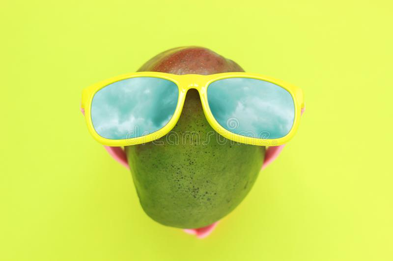 Ripe juicy green and red mango in sunglasses on pastel yellow background.Copy space. minimalistic style. Ripe juicy green and red mango in sunglasses under the royalty free stock photography