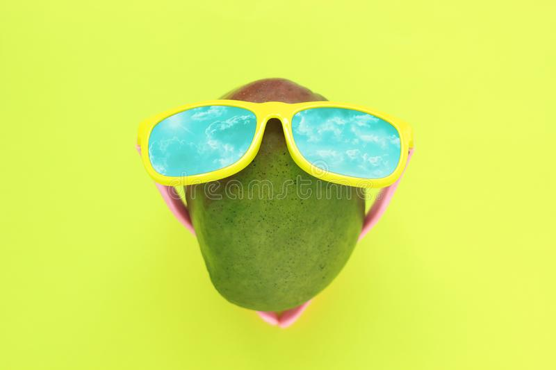 Ripe juicy green and red mango in sunglasses on pastel yellow background.Copy space. minimalistic style. Ripe juicy green and red mango in sunglasses under the royalty free stock photos
