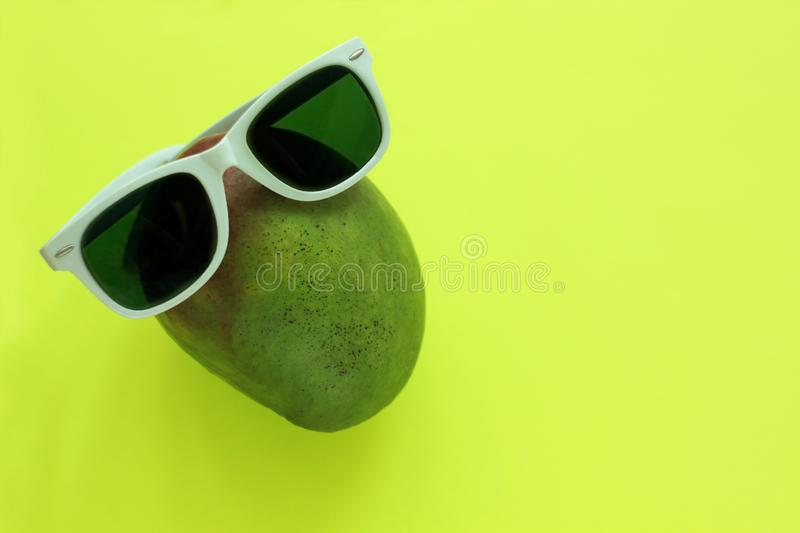 Ripe juicy green and red mango in sunglasses on pastel yellow background.Copy space. minimalistic style. Ripe juicy green and red mango in white sunglasses on stock image