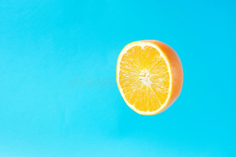 Ripe Juicy Halved Orange Floating Levitating in the Air on Light Blue Background. Vitamins Healthy Diet Summer Detox Vegan royalty free stock images