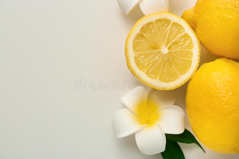 Ripe juicy lemons and exotic flower on white background, top view stock photo