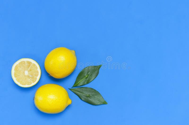 Ripe juicy lemons and green leaves on bright blue background. Lemon fruit, citrus minimal concept, vitamin C. Creative summer food. Minimalistic background royalty free stock photo