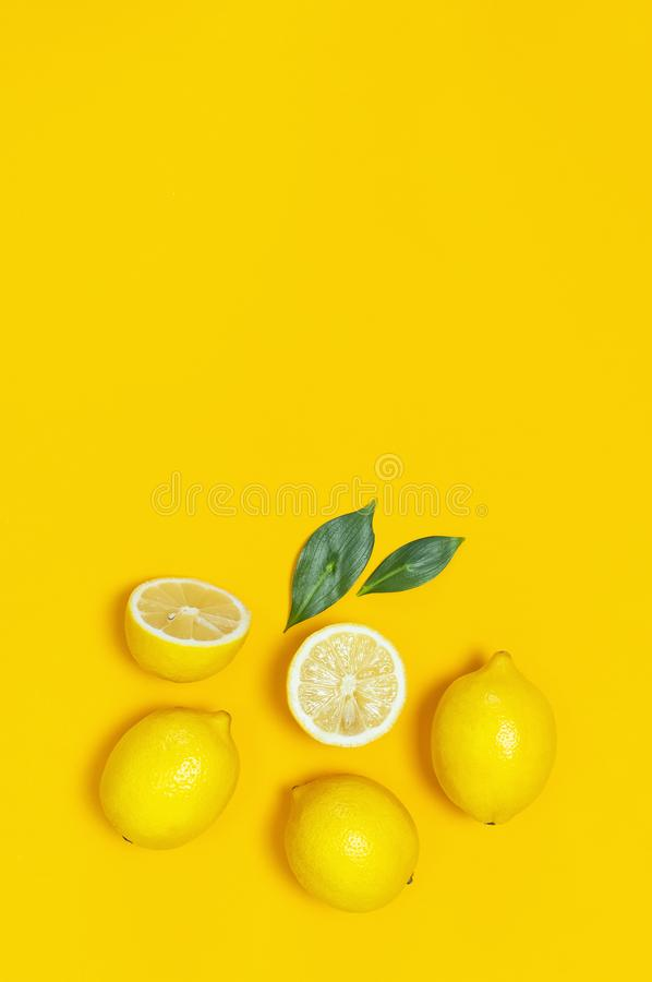 Ripe juicy lemons and green leaves on bright yellow background. Lemon fruit, citrus minimal concept, vitamin C. Creative summer. Food minimalistic background royalty free stock photography