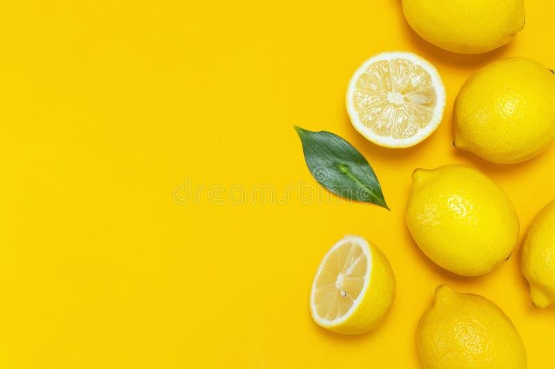 Ripe juicy lemons and green leaves on bright yellow background. Lemon fruit, citrus minimal concept, vitamin C. Creative summer. Food minimalistic background royalty free stock photos