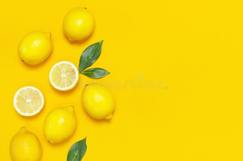 Ripe juicy lemons and green leaves on bright yellow background. Lemon fruit, citrus minimal concept, vitamin C. Creative summer. Food minimalistic background stock photography