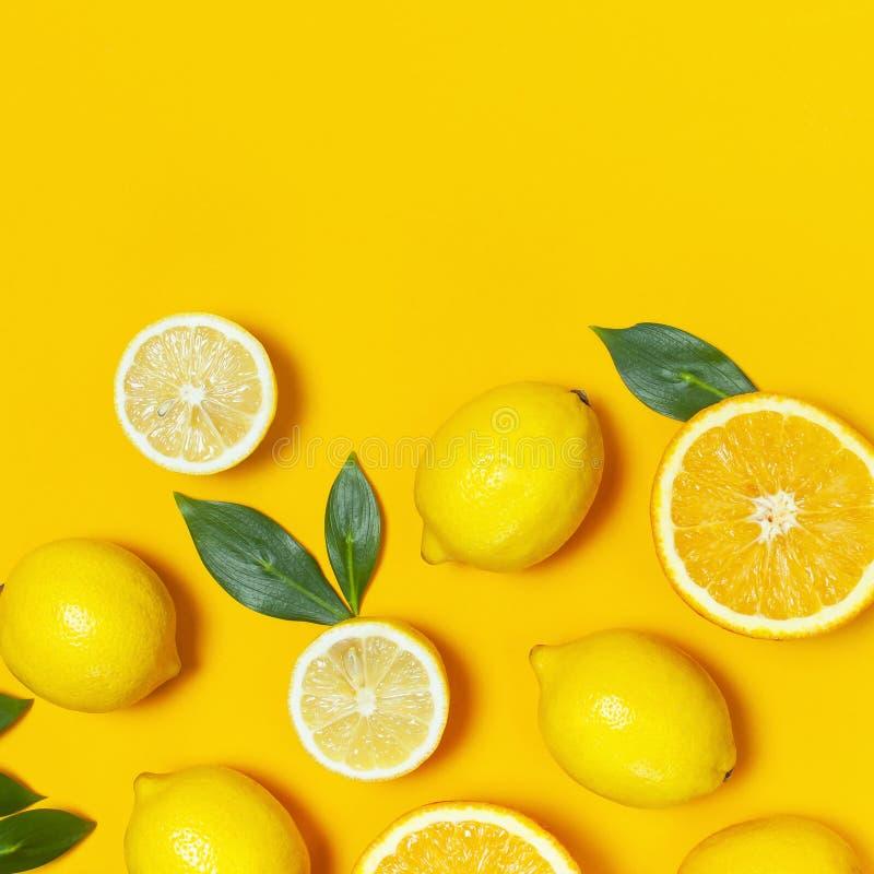 Ripe juicy lemons, orange and green leaves on bright yellow background. Lemon fruit, citrus minimal concept, vitamin C. Creative stock images
