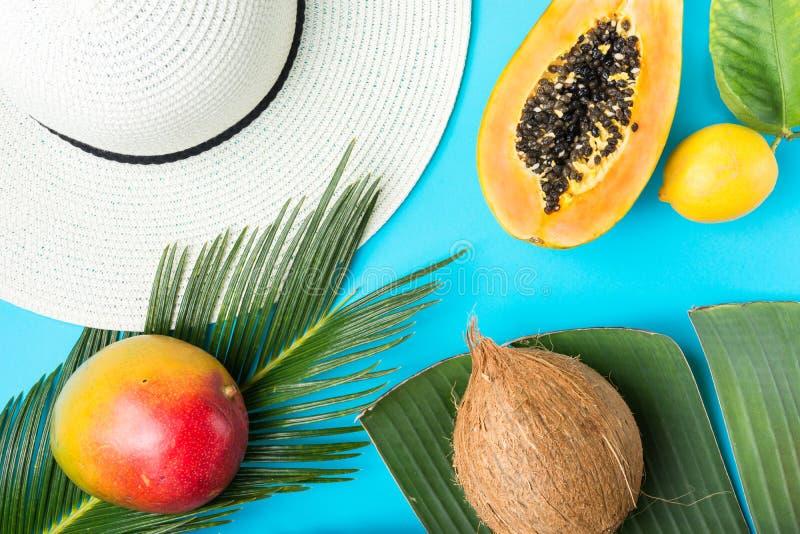 Ripe juicy mango halved papaya coconut on big palm leaf. Straw beach sun hat on blue background. Summer vacation fashion. Ripe juicy mango halved papaya coconut stock photo
