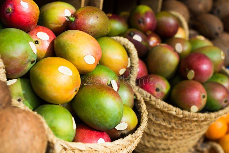 Ripe juicy mango in wicker baskets on market counter stock image