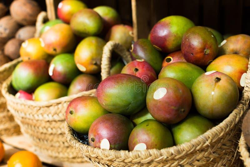 Ripe juicy mango in wicker baskets on market counter royalty free stock image