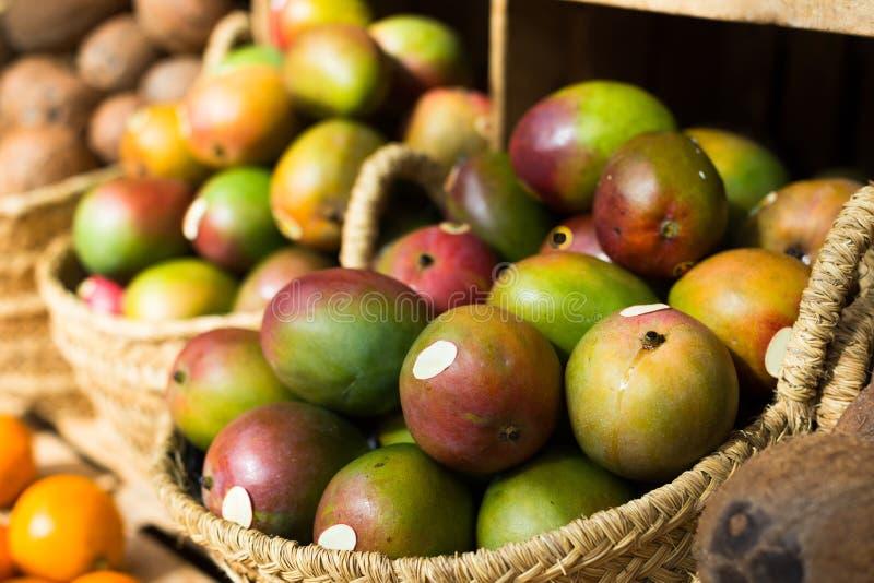 Ripe juicy mango in wicker baskets on market counter stock photography