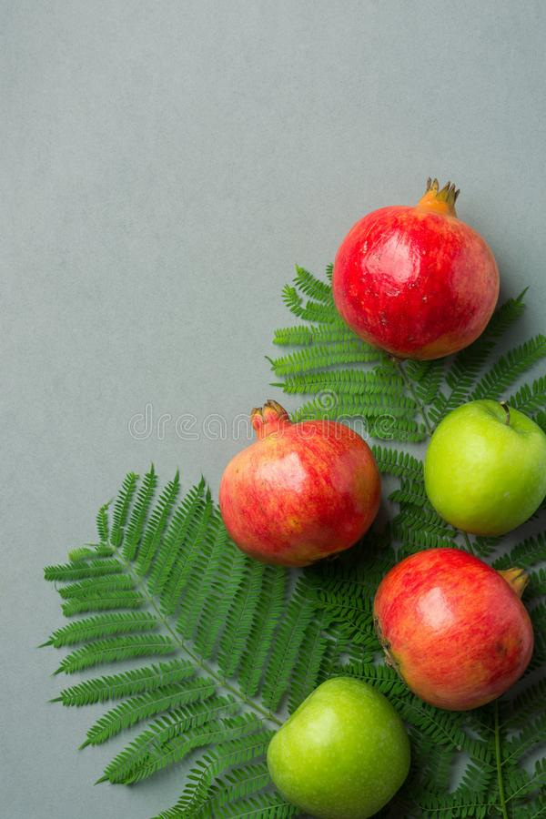 Ripe juicy organic bright red pomegranates green apples fern branches on grey stone background. Fall produce harvest royalty free stock photos