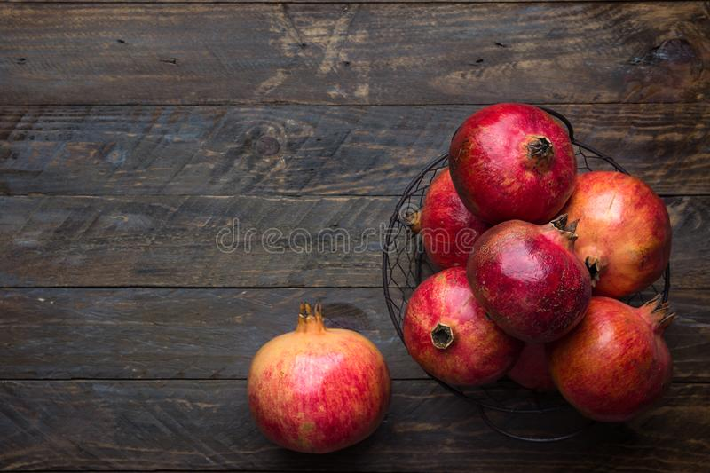 Ripe juicy organic bright red pomegranates in metal wicker basket on reclaimed plank barn wood background. Fall produce harvest royalty free stock image